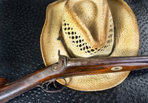 Antique Double Barrel Shot Gun and Straw Hat.