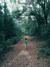 child running along a path in a forest