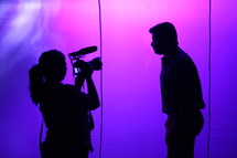 silhouette of woman with a video camera and a man