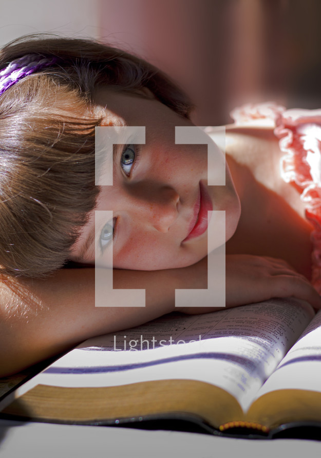 a girl child resting her head on the pages of a Bible