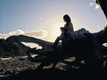 woman sitting on driftwood on a beach