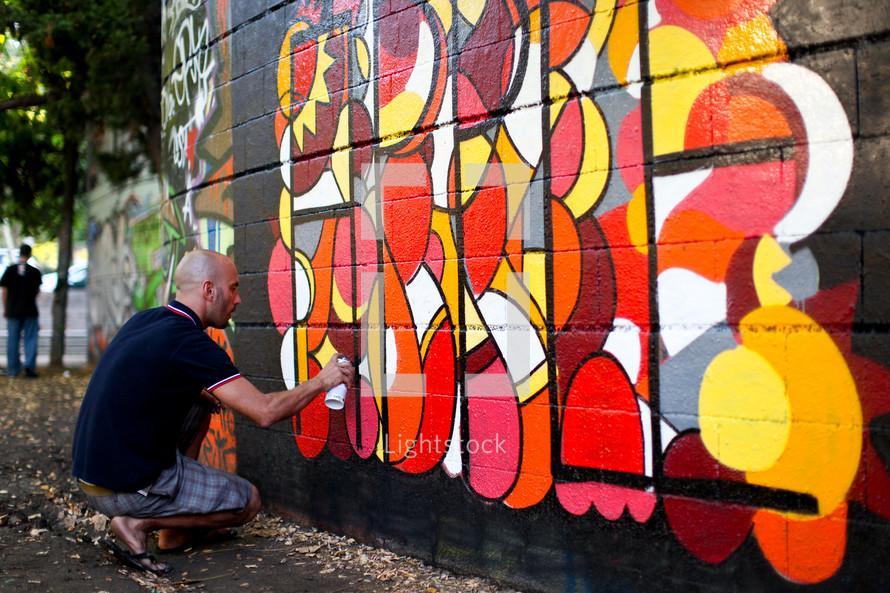 An artist spray painting on a wall