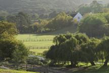 fenced farmland and a farmhouse on a hill