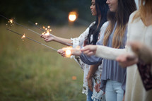 group of young women holding sparklers in a field