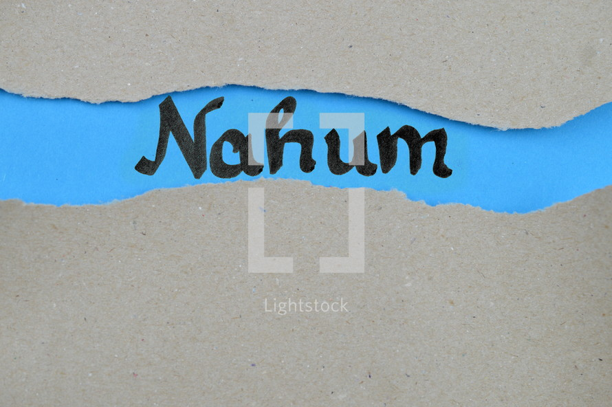 Nahum - torn open kraft paper over blue paper with the name of the prophetic book Nahum