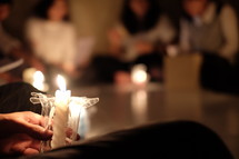 group of young woman holding candles praying