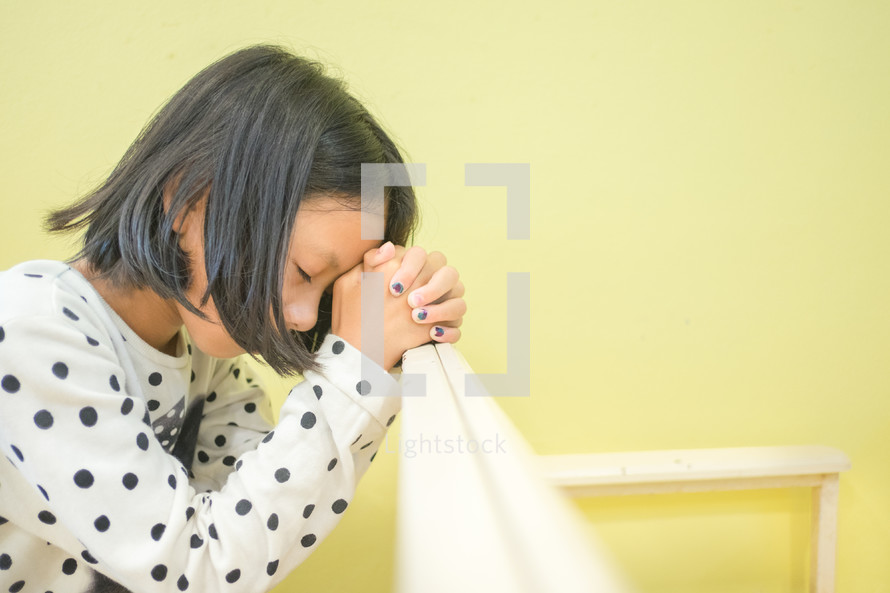 praying child with head bowed
