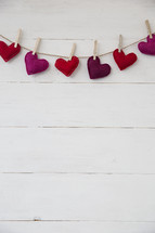 felt hearts hanging on a clothesline.