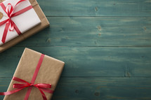 Gifts wrapped in brown paper on a teal table.