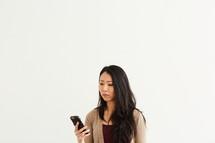 an upset woman looking at a cellphone screen