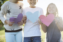 children holding paper hearts outdoors