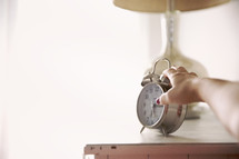 woman's hand reaching for an alarm clock.