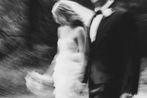 blurry image of a bride and groom walking holding hands