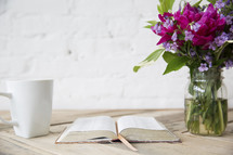 coffee mug, open Bible, and flowers in a vase on a wood table