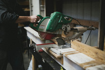 man sawing a wood board