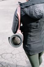 woman walking carrying a yoga mat