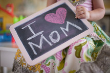 a little girl holding a chalkboard sign that reads I heart mom
