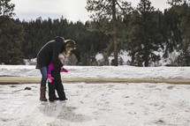 mother and child in a snowsuit playing outdoors