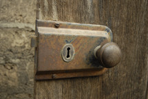A rusty doorknob and lock on an old wooden door.
