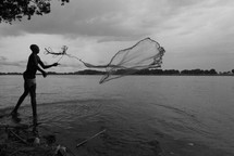 Sudanese fisherman casting his net into the River Nile.