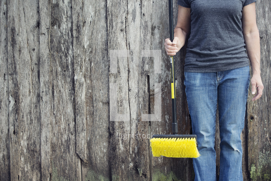 woman holding a push broom in front of a fence