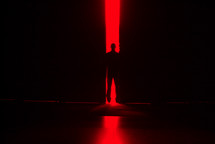 Man standing in a doorway with bright red light behind.