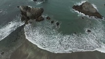 aerial view over tide washing onto a beach
