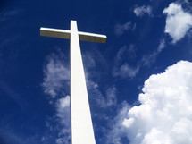 A large white cross stretches out against a blue sky surrounded by clouds and the earth's atmosphere as it stretches out between Heaven and Earth to show the power and reach of the gospel message to all the earth that Jesus was crucified, died then resurrected from the dead three days later overcoming the grave, death and sin for all of mankind for all ages.