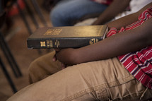 boy child holding a Bible in his lap