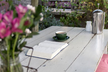 coffee, flower vase, and open Bible on a wood table