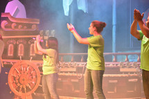 youth on stage leading a group at VBS