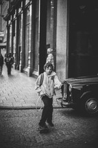 Boy riding a skateboard across a cobblestone street.