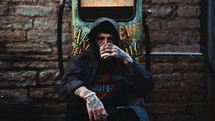 man with tattooed coffee sitting on a curb drinking coffee