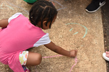 a child drawing with sidewalk chalk