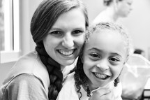 smiling teen girl holding a young girl at VBS