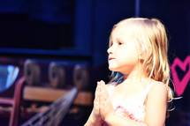 young girl with praying hands at VBS