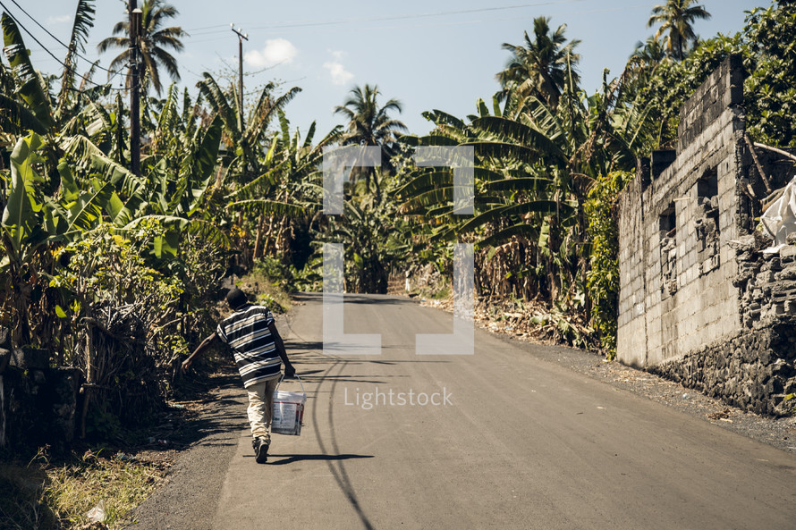 man carrying a bucket on an African street
