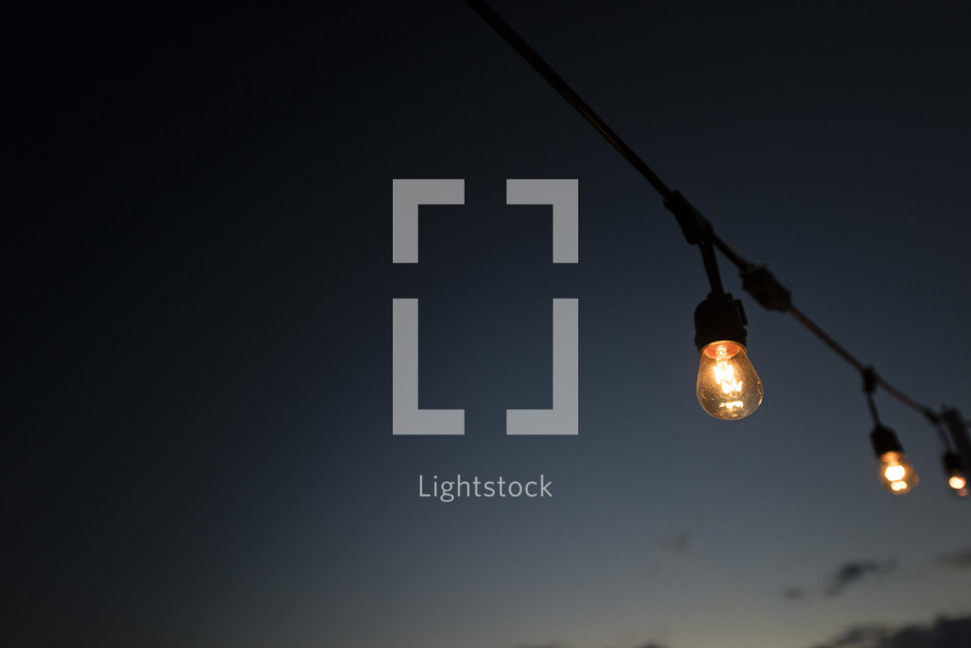 hanging lightbulbs outdoors at night