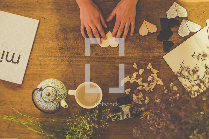 Someone making paper hearts on a wooden table with a tea kettle and a tea cup.