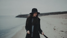 a young woman in a trench coat and hat standing on a beach shore