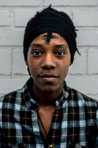 a cross in a ashes on a woman's forehead