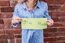 a young woman holding a give thanks sign