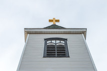 Looking up at church steeple with golden cross on top