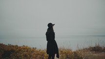 a young woman in a trench coat and hat standing on a coastal shore