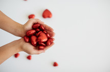 cupped hands holding red Valentines hearts