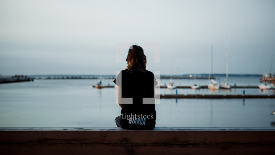 a girl sitting at a harbor looking out at the boats