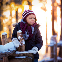 a boy leaning on a fence with snow