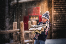 a boy carrying firewood in the snow