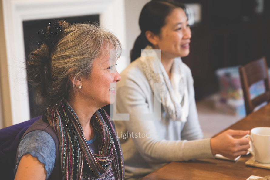Asian women sitting at a table with mugs of tea