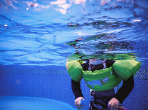 A child swimming in a pool wearing a lifejacket.